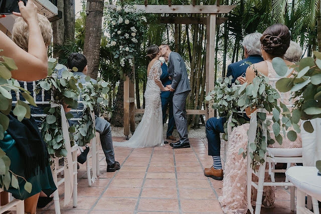 Just married Bride and Groom kissing Ceremony The Manor on St Lucie Crescent Wedding captured by Stuart Wedding Photographer Heather Houghton Photography
