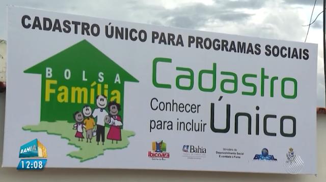 Foto da placa de onde faz cadastro para programas sociais, com desenho do bolsa familia de cor verde e amarela e uma familia e logos do municipio de demais entidades do governo