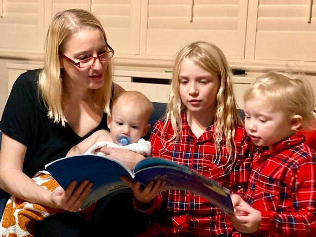 3 children and a mum Reading The Night Before Christmas together on Christmas eve
