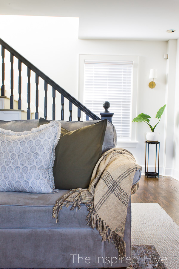 Sofa, patterned pillows, and historic staircase