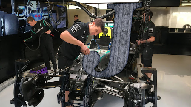 A mechanic working on a massive letter J in the Mercedes pit garage