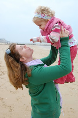 picture of steph wearing a green jumper on a beach holding Daisy in her arms. Daisy is three years old and smiling.