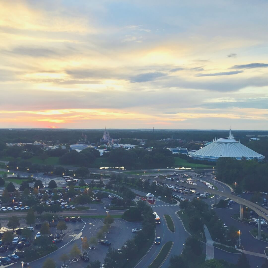A photo of Magic Kingdom from the top of a building. The sun sets on the horizon turning the sky into an orange colour. Space Mountain can be seen on the right of the photo, its white dome distinctive. Cinderella's Caslte is in the middle of the photo, small but visible.
