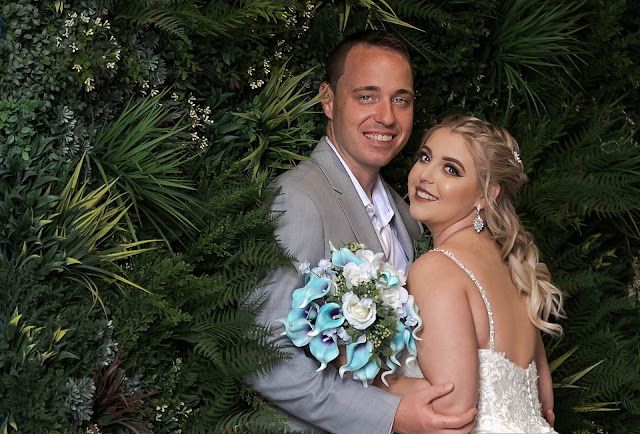 Bride and Groom holding each other in the bushes with blue bouquet
