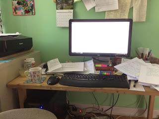 Mug of tea at a cluttered computer desk
