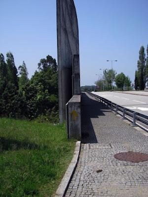 Seta do caminho de Santiago de Compostela num poste na beira da estrada
