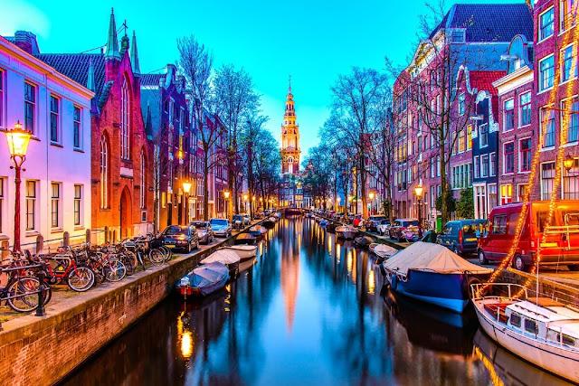 """Nổi tiếng với hệ thống kênh rạch chằng chịt, những ngôi nhà nhỏ xinh xắn dọc theo những con phố, và đặc biệt là hình tượng cối xay gió, Amsterdam là điểm đến thơ mộng đáng mơ ước của du khách thế giới, được ví như Venice của Ý. Bên cạnh đó, những quán cà phê bán """"cỏ"""" hay khu phố đèn đỏ nhộn nhịp thu hút sự tò mò của 4 triệu du khách mỗi năm."""