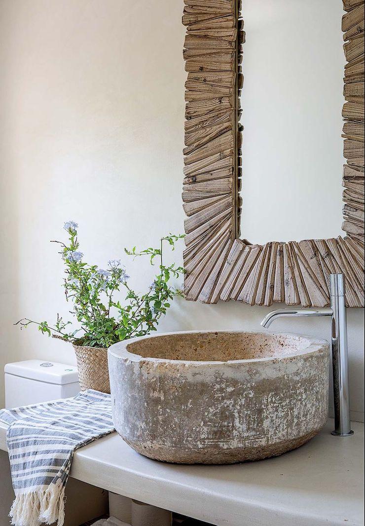 Baño de estilo mediterráneo con espejo reciclado.