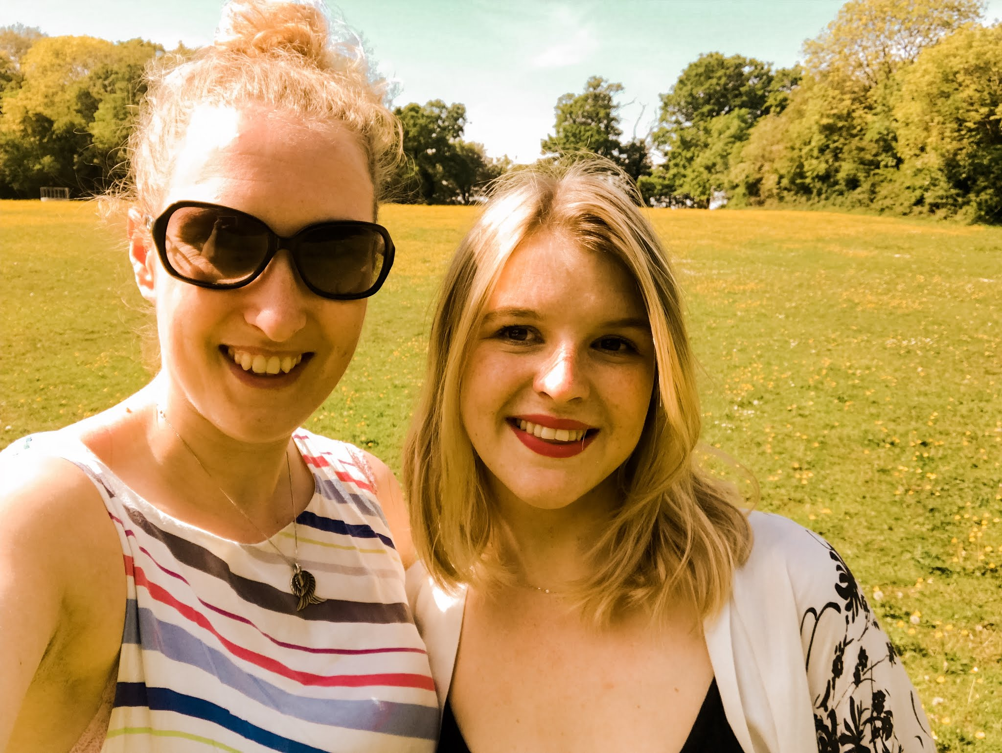 Two friends smiling in a field during Summer 2019