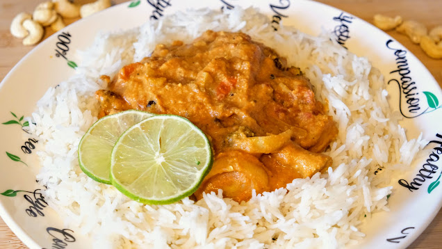 Butter curry on a plate with white rice and slices of lime