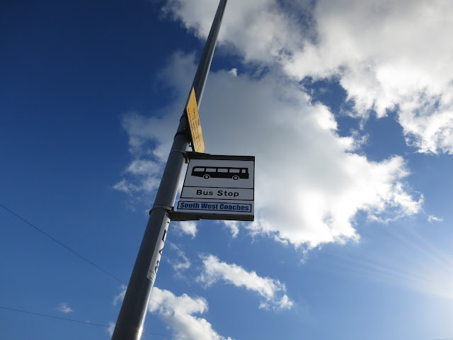 Bus stop against blue sky with white clouds.