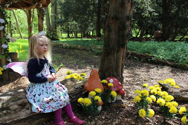 A girl dressed as a fairy sat on a log surrounded by fake flowers at Audley End Miniature railway