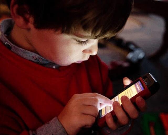 Anak kecil sedang menggunakan iPhone