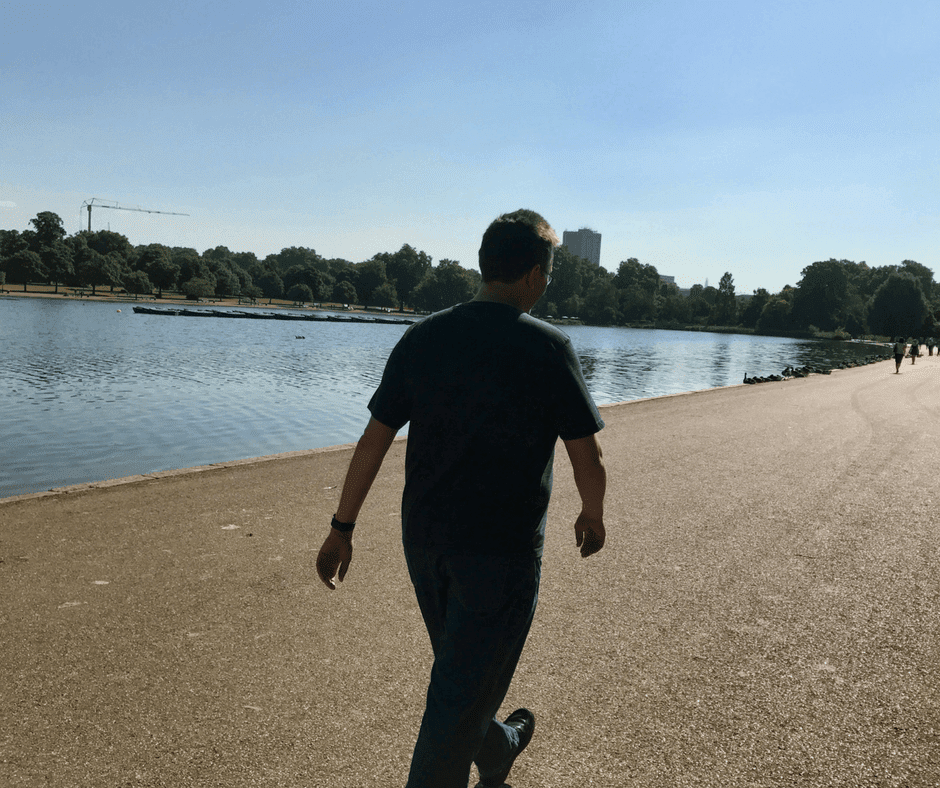 Man walking along footpath next to a lake in Hyde Park
