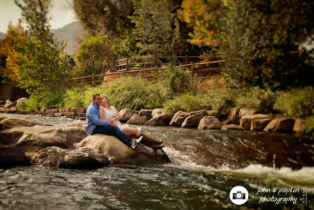 a couple sits along a river for their engagement session photograph in golden colorado