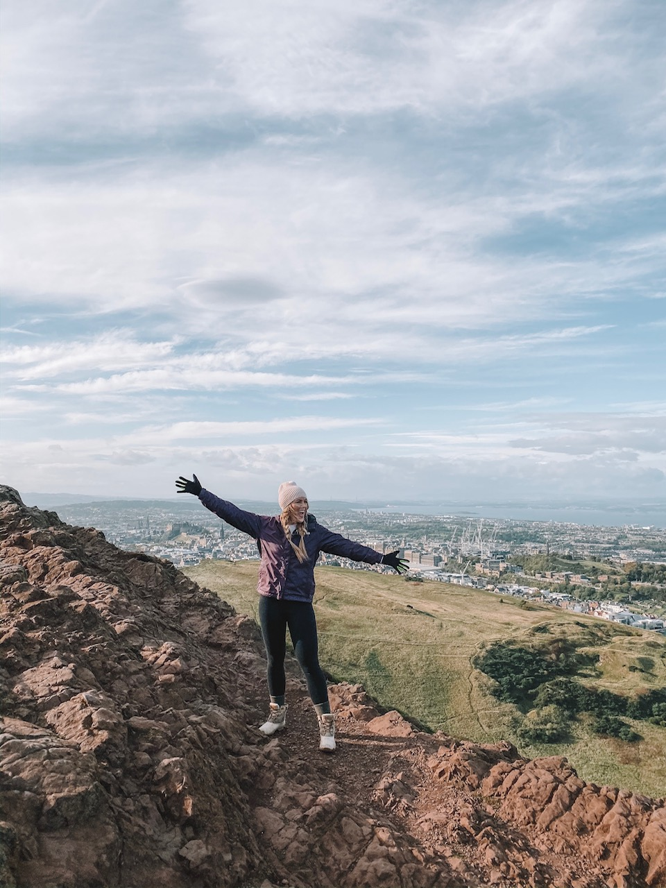 travel blogger Amanda Martin hikes atop Arthur's Seat in Edinburgh
