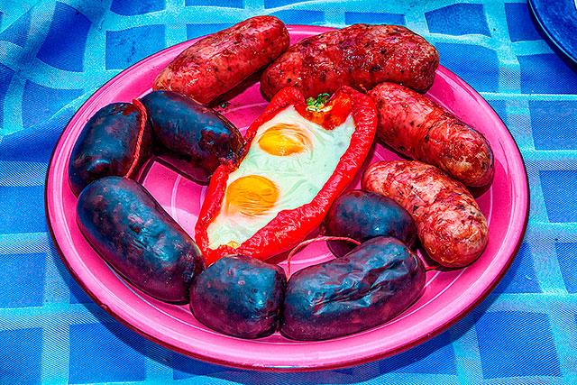 Plato conteniendo chorizos y morcillas asada y un pimiento con huevos fritos.