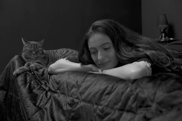 model on a bed with a cat