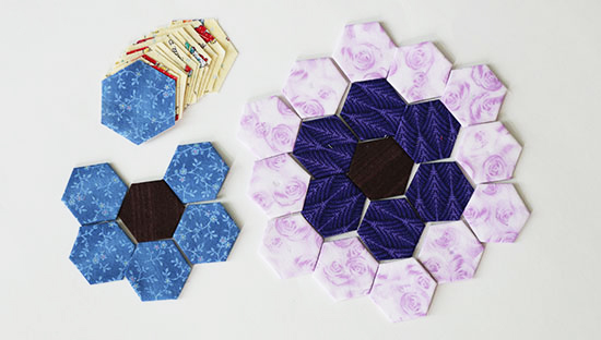 Precut hexies next to basted hexies placed as hexagon flower blocks on a white background.
