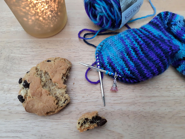 A flatlay showing a candle through a speckled glass holder, a half-eaten chocolate biscuit and a half-knitted blue and purple sock