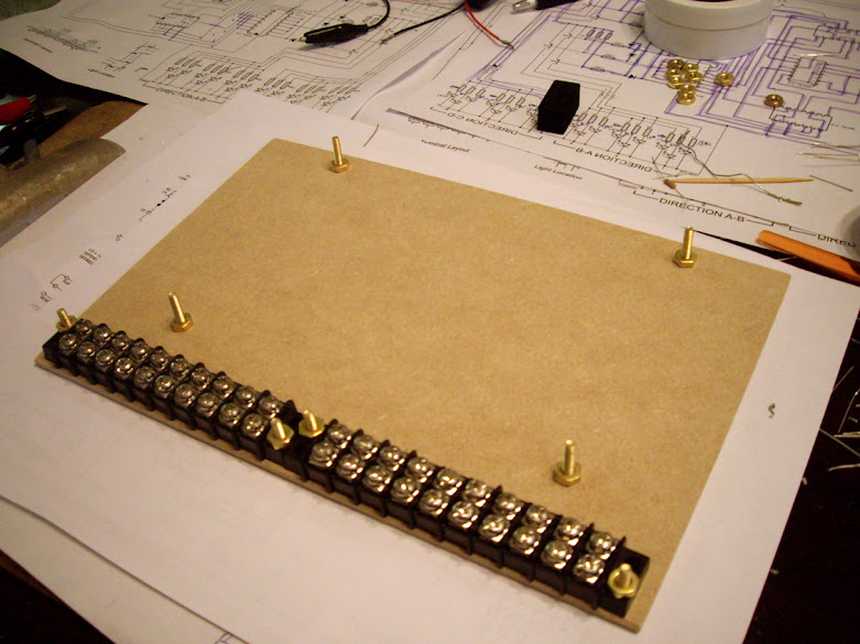 Terminal strips and brass support bolts fastened to a hardboard base