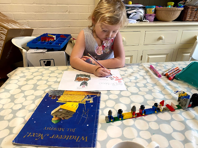 A 4 year old in a party dress doing some school work at a dining table with the Whatever Next book in front of her and some lego