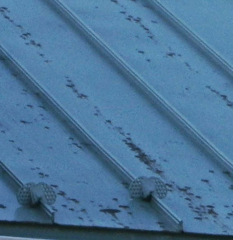 Ten year old standing seam metal panels with rust breaking through