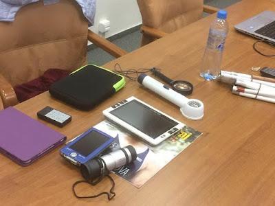 Na stole leží pomůcky pro zrakově postižené (lupy, monokulár, VPN, bílá hůl...)