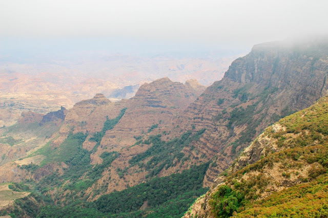 view of the surrounding mountains and canyons from our hike in the simien mountains on a foggy day