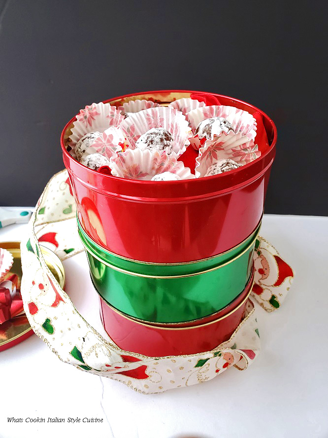 this is a pretty red tin with poinsetta paper liners and rum balls in the papers to fill the red Christmas tin.