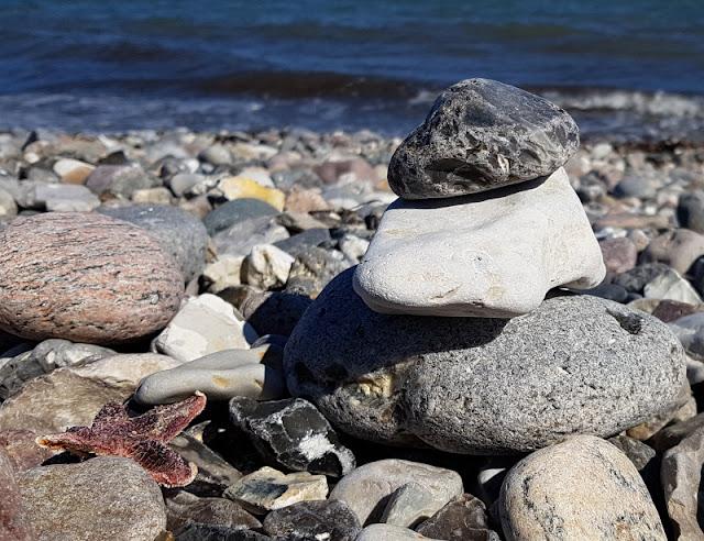 Küsten-Spaziergänge rund um Kiel, Teil 3: Raps, Steine und Meer bei Hohenfelde. Ein Steinturm zum Gedenken errichtet an einem Steinstrand.