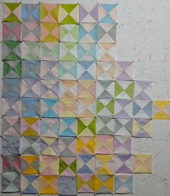 3.5-inch hourglass blocks are placed on the design wall as they are sewn and pressed.