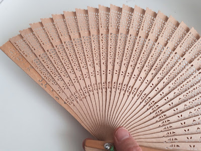 Hand holding a wooden fan.