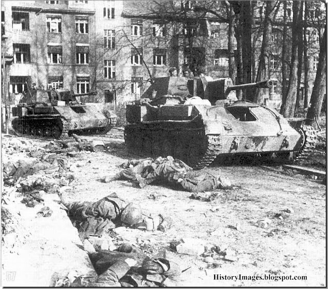 Russian tanks trundle past dead German soldiers. Belarus 1944