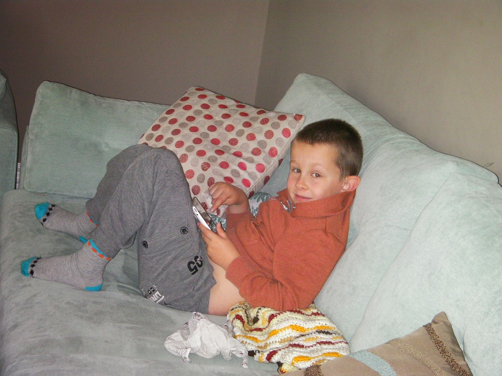 kid playing minecraft on tablet on sofa