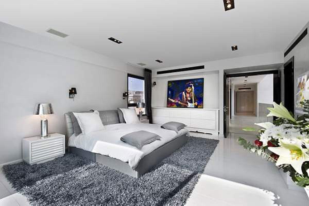 غرفة نوم رمادية فاتحة مع قطعة سجادة تحت السرير غامقة