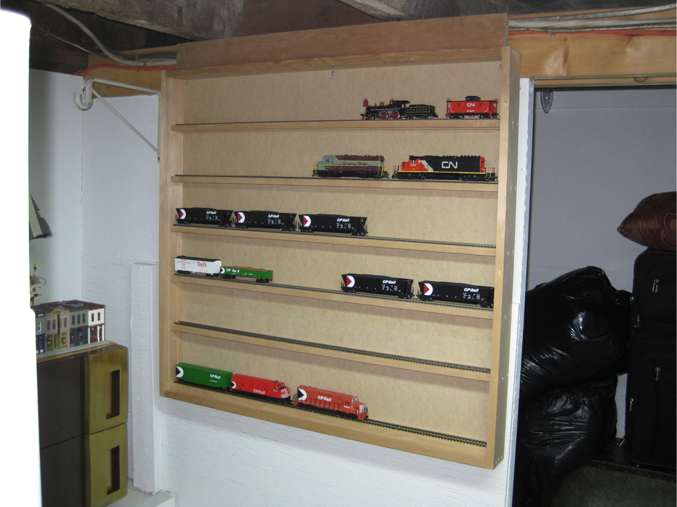 Scratch built model train display case with 6 shelves installed on a wall with locomotives and rolling stock