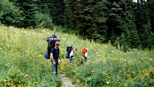a father leading daughters while backpacking