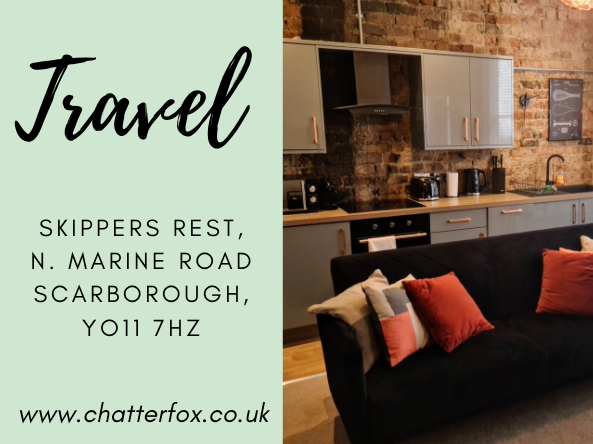 Image of the industrial style interior of Skippers Rest holiday rental accommodation in Scarborough. The image shows the living are with grey gloss fitted kitchen and black velvet sofa bed with bright coloured cushions. The right of the image is a title that reads 'Travel, Skippers Rest, North Marine Road, Scarborough YO11 7HZ, www.chatterfox.co.uk'