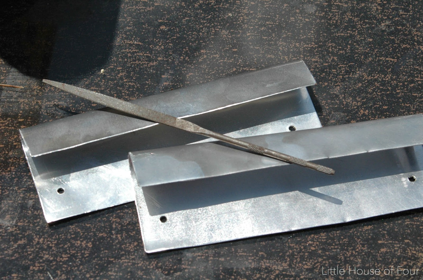 Smoothing metal bin pulls with a metal file