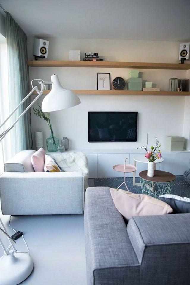 salón decorado en tonos pastel con tv plana colgada en la pared y grandes estanterías voladas