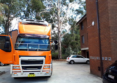 A big orange truck parked outside a block of flats.
