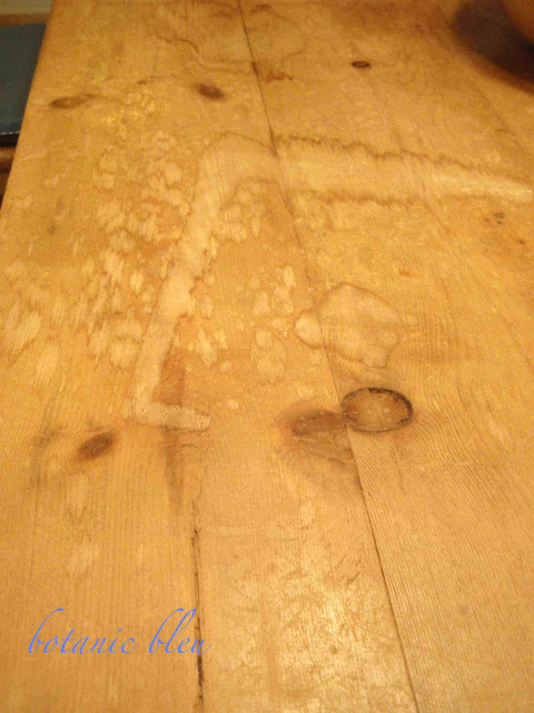 Severe water damage to a reclaimed pine boards table