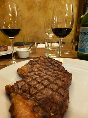 A steak with visible criss-cross char lines and two glasses of wine behind it.