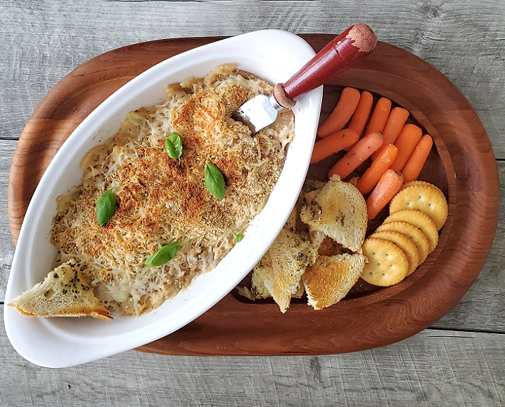 this is a hot crab dip on a wooden cutting board filled with assorted crackers, vegetables and garlic bread to dip into this hot crab dip