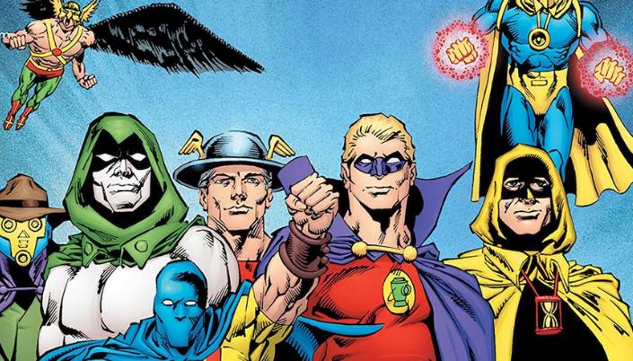 Imagem: uma ilustração das HQs em que se vê diversos heróis da Sociedade da Justiça da América, da esquerda para a direita, o Gavião Negro, um homem musculoso com um capacete de gavião dourado, um par de asas e um uniforme composto por calças verdes e botas vermelhas. Abaixo, o