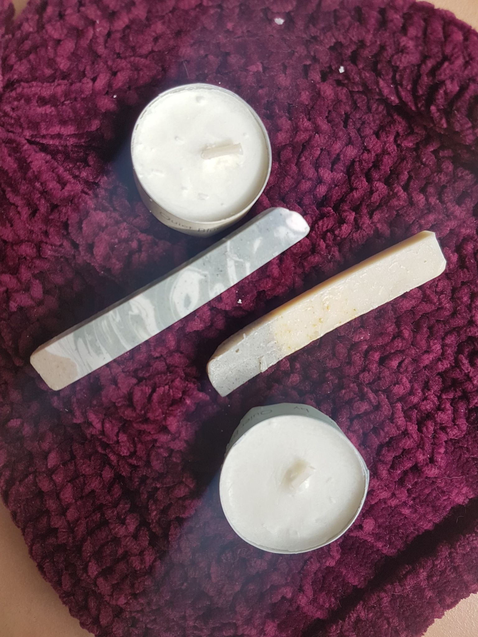 Quiet Blue sample size Candles and Soaps on a textured wooly maroon coloured hat