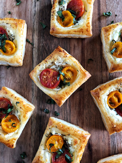 puff pastry with goat cheese, roasted tomatoes and herbs on a wooden background