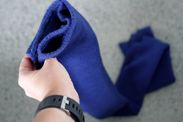 Looking at a small but very long piece of blue polar fleece fabric from the selvage edge