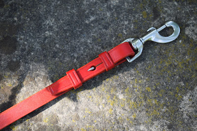 Dog leash snap-hook end detail, red leather and stainless steel